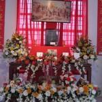 The Ancestor Veneration Altar with picture of Chinese martyrs above and an urn for incense sticks